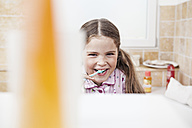Germany, North Rhine Westphalia, Cologne, Portrait of girl brushing teeth in bathroom - FMKYF000464
