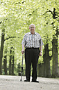 Germany, North Rhine Westphalia, Cologne, Portrait of senior man with walking stick in park, smiling - JAT000117