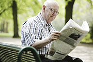 Germany, North Rhine Westphalia, Cologne, Senior man reading newspaper on bench in park - JAT000147