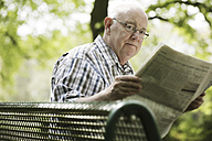 Germany, North Rhine Westphalia, Cologne, Portrait of senior man reading newspaper on bench in park - JAT000149