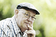 Germany, North Rhine Westphalia, Cologne, Senior man with cap and glasses in park, close up - JAT000123
