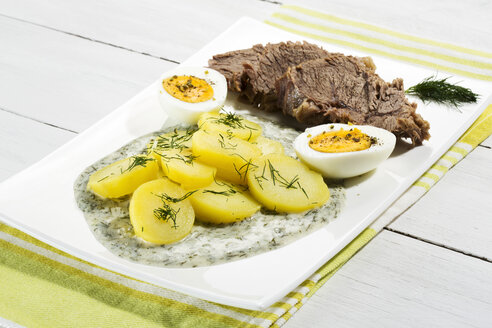 Beef with dill sauce, potatoes and boiled egg on plate, close up - MAEF007086