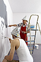 Germany, Grandfather and grandson painting wall - LAF000115