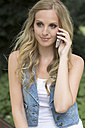Germany, Oberhausen, Young woman talking on mobile phone, smiling - GDF000139