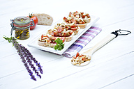 Plate of bruschetta with tomatoes, white shimeji mushrooms, herbs and olive oil on wooden table, close up - MAEF007042