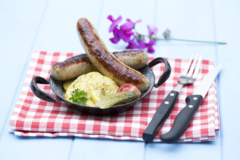 Fried sausages with potatoes and pickled gherkin on wooden table, close up - MAEF007106