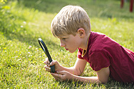 Germany, Bavaria, Boy looking through magnifying glass in garden - SARF000078
