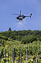 Germany, Rhineland Palatinate, View of helicopter spraying wine in vineyard - AM000790