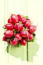 Bunch of red radishes on wooden table, close up - MAEF007060