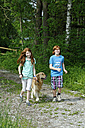 Germany, Bavaria, Gir and boy walking with dog - LB000253