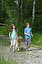 Germany, Bavaria, Gir and boy walking with dog - LB000253