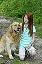 Germany, Bavaria, Girl caring dog, smiling - LB000251