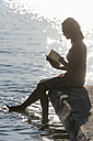 Germany, Bavaria, Mature woman reading book at Lake Stamberg - TCF003524