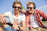 Germany, two young men wearing head phones, listening to music - GDF000155
