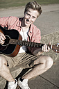 Germany, Young man playing guitar in park - GDF000165