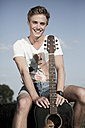 Germany, Young man sitting in park, holding guitar - GDF000175