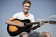 Germany, Young man playing guitar in park - GDF000177