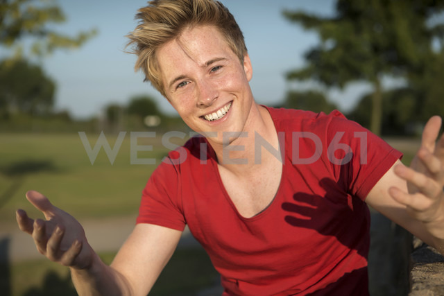 Germany, Young man sitting in park, gesturing - GDF000190