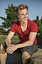 Germany, Young man sitting in park, smiling - GDF000186