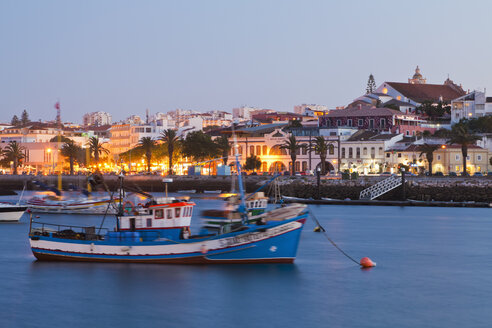 Portugal, Lagos, View of fishing boat at harbour and city in background - WDF001888