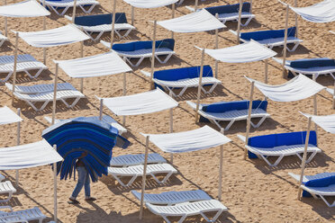 Portugal, Albufeira, Preparing beach loungers in morning - WD001759