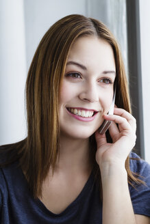 Germany, Bavaria, Munich, Young woman talking on mobile phone, smiling - SPOF000449