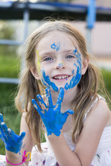 Germany, Bavaria, Portrait of girl playing with finger paint, smiling - SARF000085