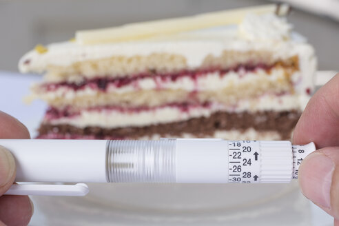 Germany, Freiburg, Mature man holding insulin while piece of cake in background - DR000063