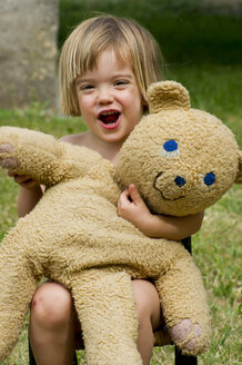 Germany, Baden Wuerttemberg, Portrait of girl playing with teddy bear, smiling - LVF000185