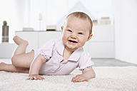 Germany, North Rhine Westphalia, Cologne, Baby girl lying on carpet, smiling - PDF000377