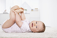 Germany, North Rhine Westphalia, Cologne, Baby girl lying on carpet, smiling - PDF000373