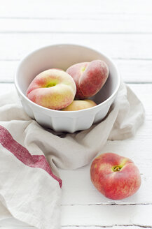 Peaches in bowl on wooden table with napkin - CZF000011