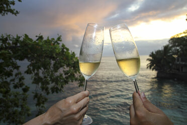 Two people holding Champagne flutes at beach - KRP000018
