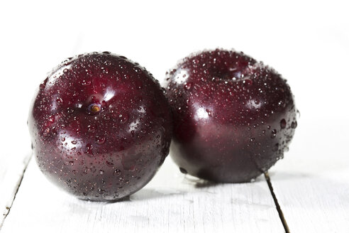 Plums on wooden table, close up - MAEF007188