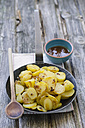 Roasted potatoes with curry sauce, close up - ODF000306