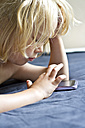 Germany, Kiel, Girl playing with smart phone on bed, close up - JFEF000183