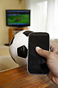 Mature man holding mobile with soccer ball and TV in background - KRP000028
