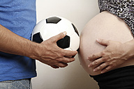 Mature man holding soccer ball in front of  pregnant woman, close up - KRP000025