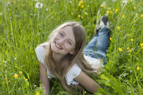 Germany, Bavaria, Portrait of girl lying on meadow, smiling - CRF002468