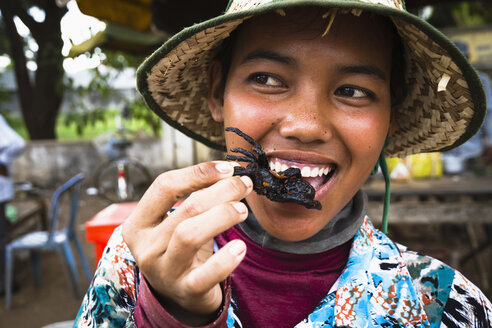 Cambodia, Woman eating fried tarantula spiders - MBE000707