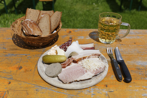 Austria, Carinthia, Plate of meat with cold cut, bread and beer glass on table - SIEF004281