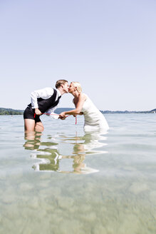 Germany, Bavaria, Tegernsee, Wedding couple standing in lake, kissing - RFF000088