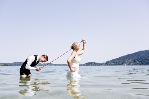 Germany, Bavaria, Tegernsee, Wedding couple standing in lake, bride holding groom on leash - RFF000101