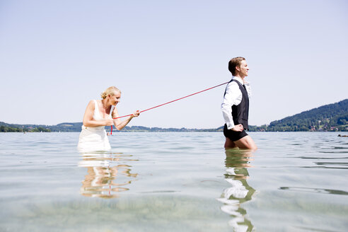 Germany, Bavaria, Tegernsee, Wedding couple standing in lake, bride holding groom on leash - RFF000089