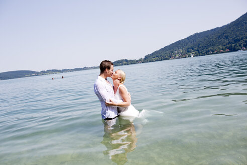 Germany, Bavaria, Tegernsee, Wedding couple standing in lake, kissing - RFF000091