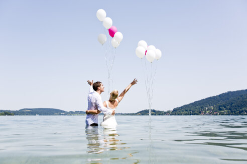 Germany, Bavaria, Tegernsee, Wedding couple standing in lake, holding balloons - RFF000093