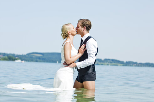 Germany, Bavaria, Tegernsee, Wedding couple standing in lake, kissing - RFF000107