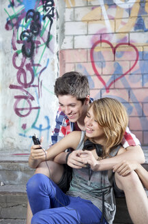 Germany, Berlin, Teenage couple using mobile phone, smiling - MVC000012