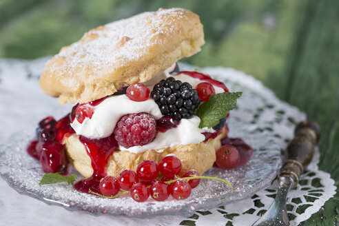 Puffs with cream and berries on wooden table, close up - STB000016