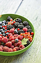 Bowl of berries on wooden table, close up - STB000024